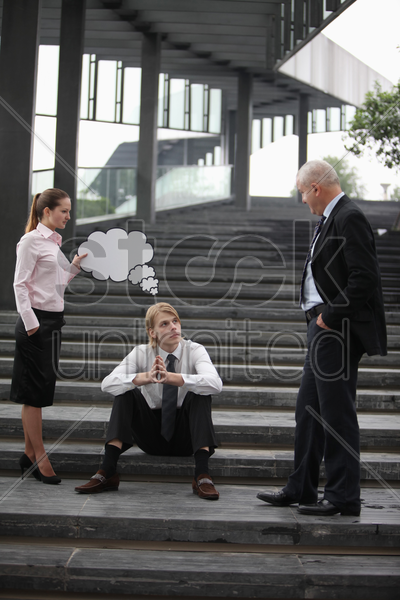 businesswoman holding thinking bubble above businessman's head, another businessman watching stock photo