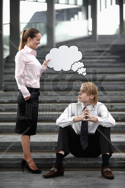businesswoman holding thinking bubble above businessman's head stock photo