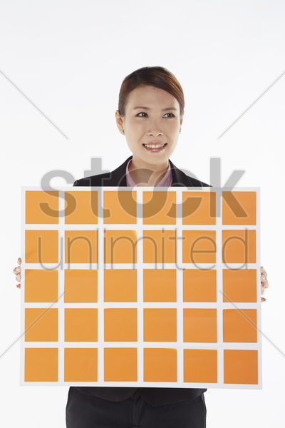 businesswoman holding up a board of adhesive notes stock photo