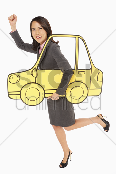 businesswoman holding up a cardboard car stock photo