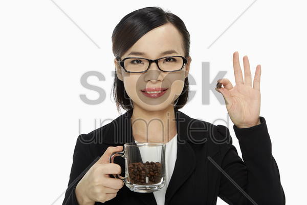 businesswoman holding up a coffee bean stock photo