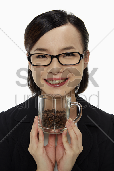 businesswoman holding up a cup of coffee beans stock photo