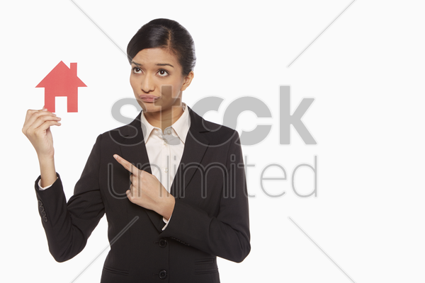 businesswoman holding up a cut out house stock photo