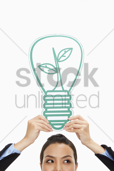 businesswoman holding up a cut out light bulb stock photo
