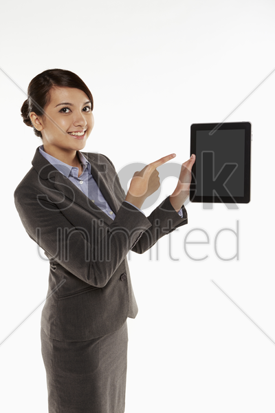 businesswoman holding up a digital tablet stock photo