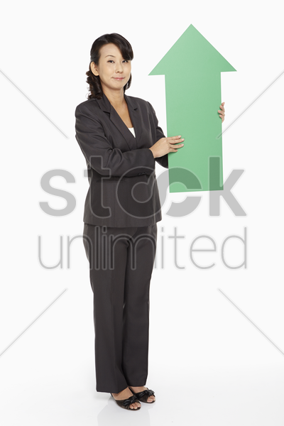 businesswoman holding up a green arrow stock photo