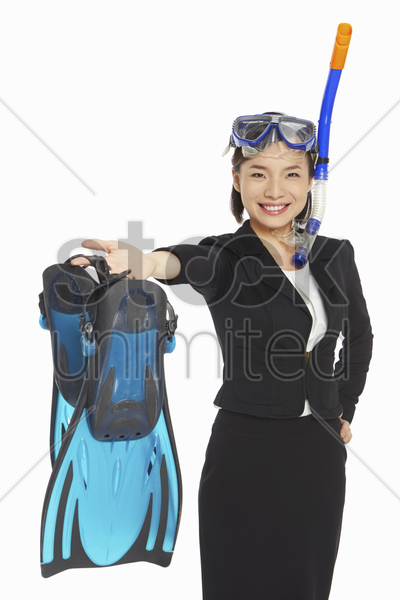 businesswoman holding up a pair of flippers stock photo