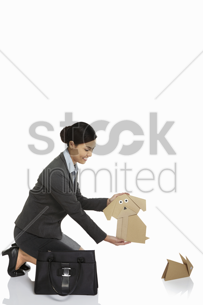 businesswoman holding up a paper dog stock photo