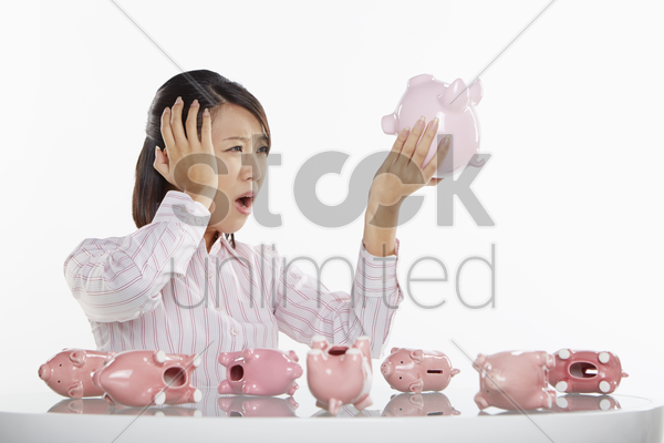 businesswoman holding up a piggy bank stock photo
