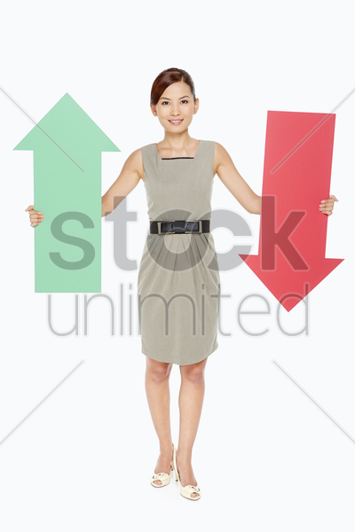 businesswoman holding up a red and green arrow stock photo