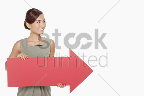businesswoman holding up a red arrow stock photo