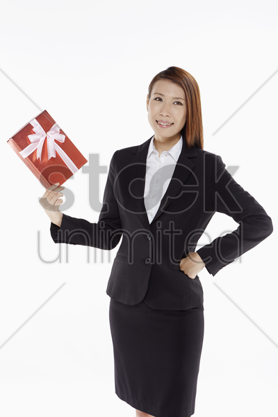 businesswoman holding up a red gift box stock photo