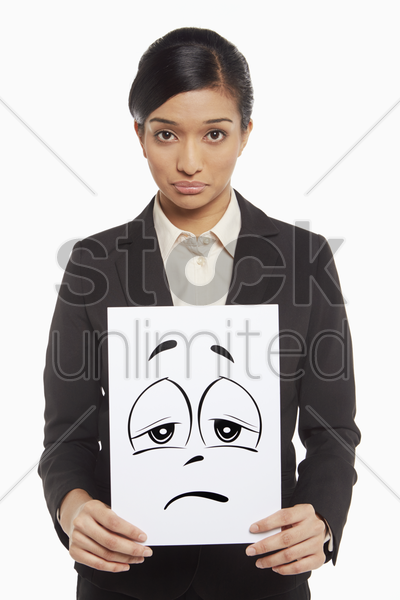 businesswoman holding up a sad face doodle stock photo