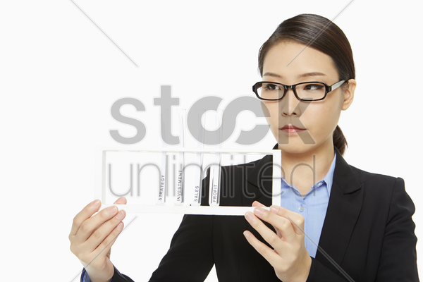 businesswoman holding up a tray of test tubes stock photo
