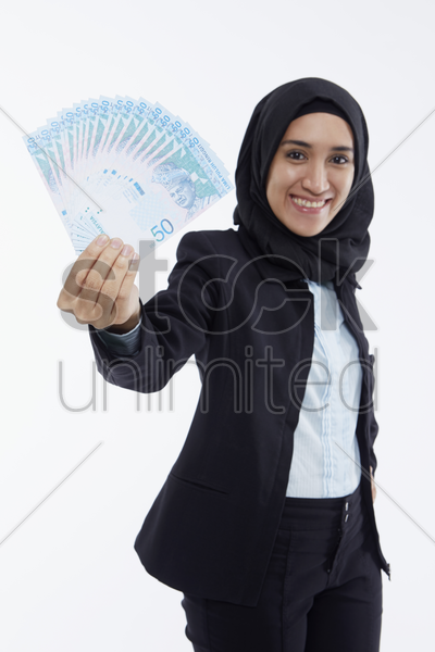 businesswoman holding up cash stock photo