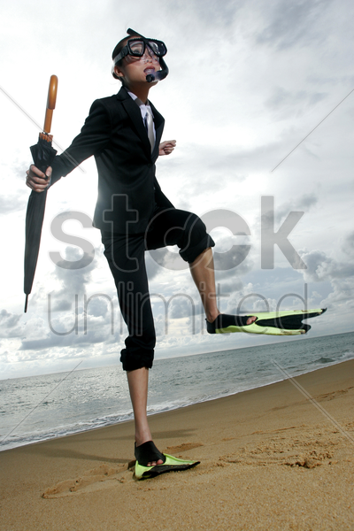 businesswoman in flippers and snorkel walking on the beach stock photo