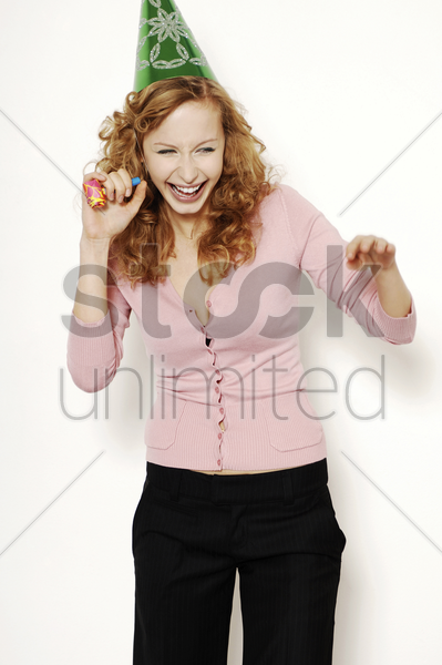 businesswoman in party hat holding a blowout stock photo
