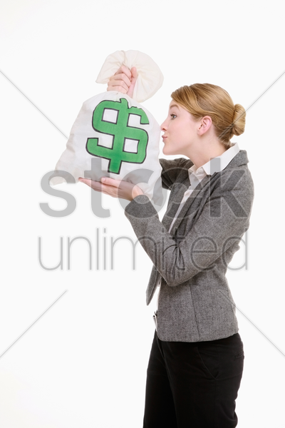 businesswoman kissing money bag stock photo
