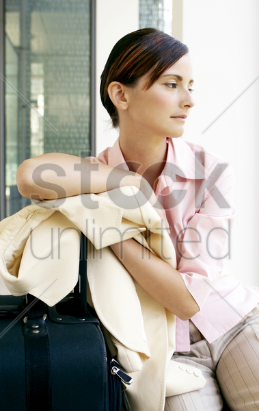 businesswoman leaning on her travelling bag stock photo