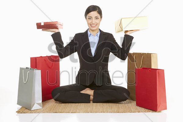 businesswoman lifting gift boxes while sitting on the floor stock photo