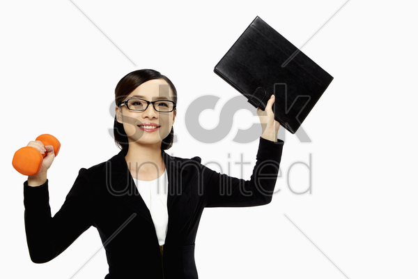 businesswoman lifting up a folder and a dumbbell stock photo