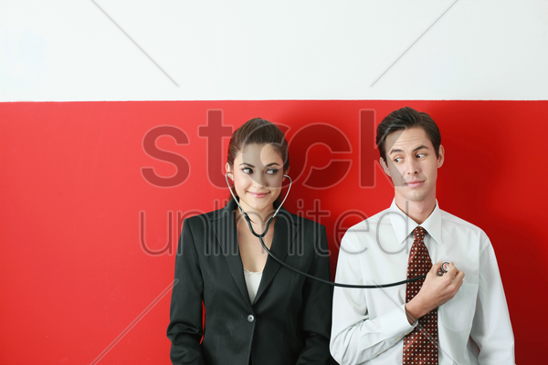 businesswoman listening to businessman's heartbeat through a stethoscope stock photo