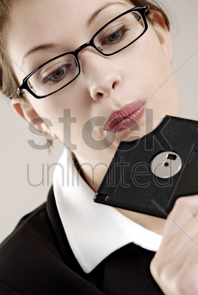 businesswoman looking at a broken diskette stock photo
