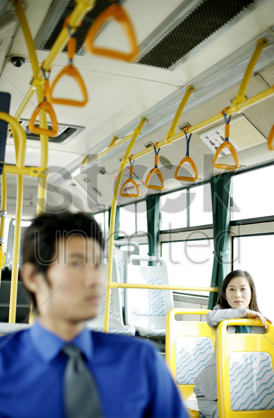 businesswoman looking at a businessman while sitting in a bus stock photo