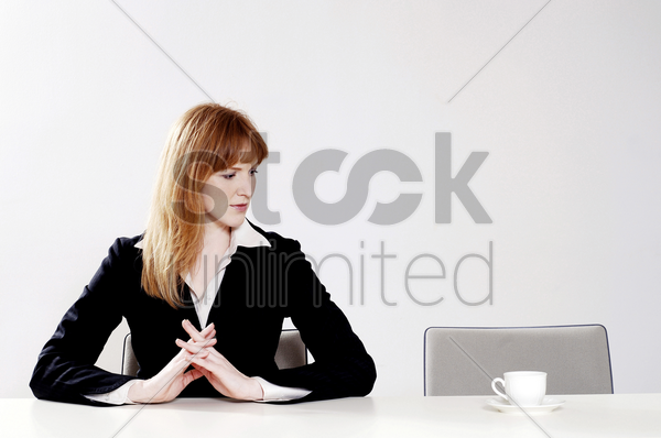 businesswoman looking at a cup of coffee beside her stock photo