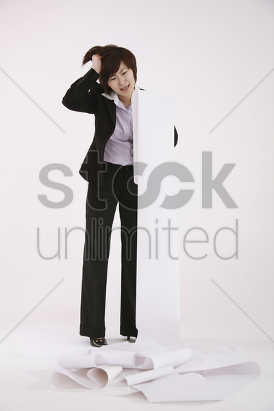 businesswoman looking at a long list of work to do stock photo