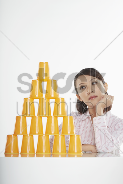 businesswoman looking at a stack of disposable cups, contemplating stock photo