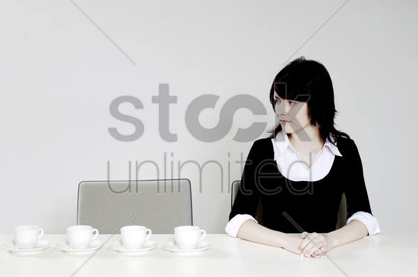 businesswoman looking at an arrangement of coffee cups stock photo