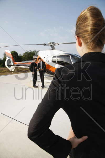 businesswoman looking at businessmen standing by the helicopter stock photo