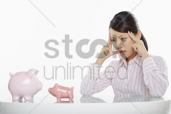 businesswoman looking at piggy banks stock photo