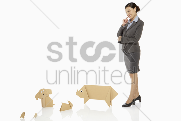 businesswoman looking over paper animals, contemplating stock photo