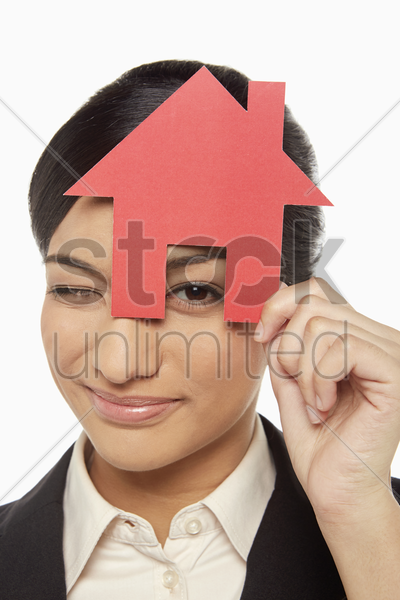 businesswoman looking through a cut out house stock photo