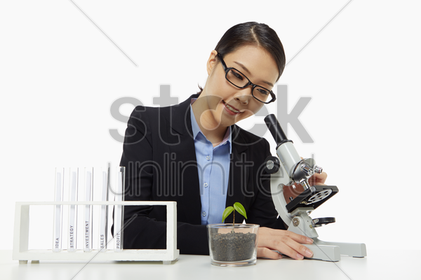 businesswoman looking through a microscope stock photo