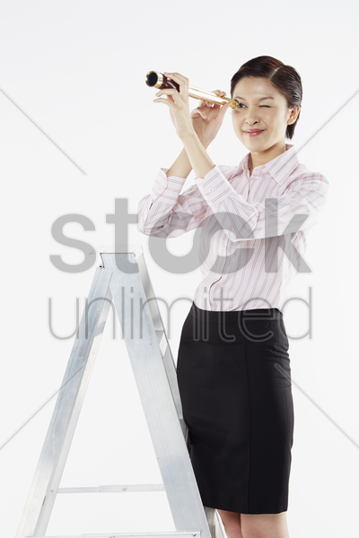 businesswoman looking through a telescope stock photo