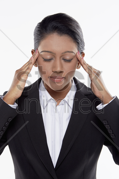businesswoman massaging her head stock photo