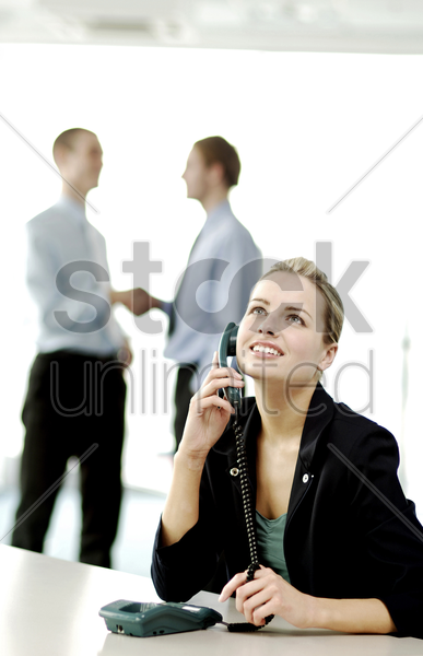 businesswoman on the phone while businessmen shaking hands on the background stock photo