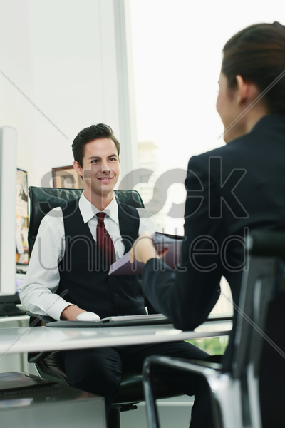 businesswoman passing document to businessman stock photo