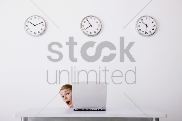 businesswoman peeping from behind a laptop stock photo