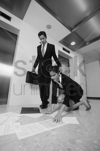 businesswoman picking up dropped papers, businessman watching stock photo