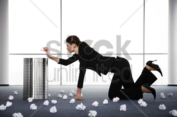 businesswoman picking up the rubbish stock photo