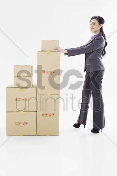 businesswoman placing a box on top of another stack of boxes stock photo