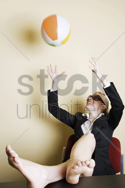 businesswoman playing with beach ball in the office stock photo