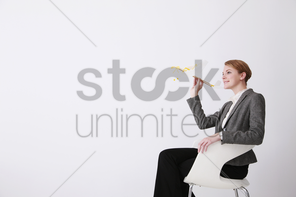 businesswoman playing with model airplane stock photo