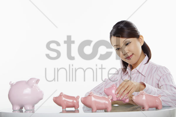 businesswoman playing with piggy banks stock photo