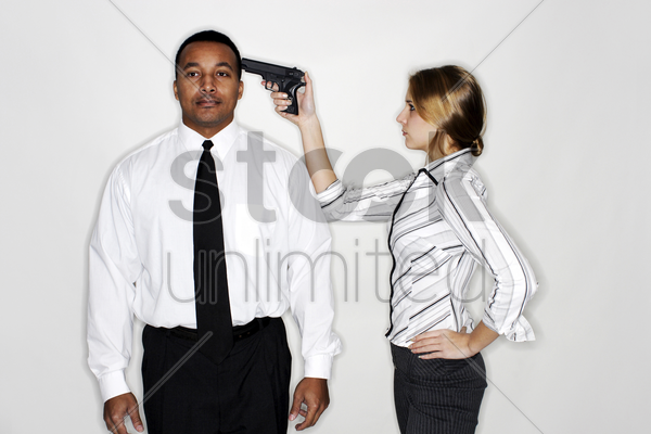 businesswoman pointing a gun at her subordinate's head stock photo
