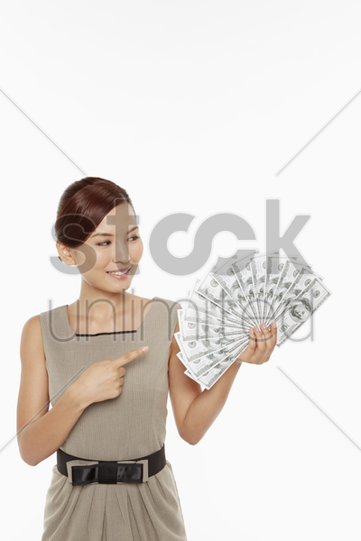 businesswoman pointing at a pile of cash stock photo